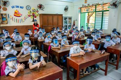 Bambini vietnamiti a scuola indossano gli scudi facciali